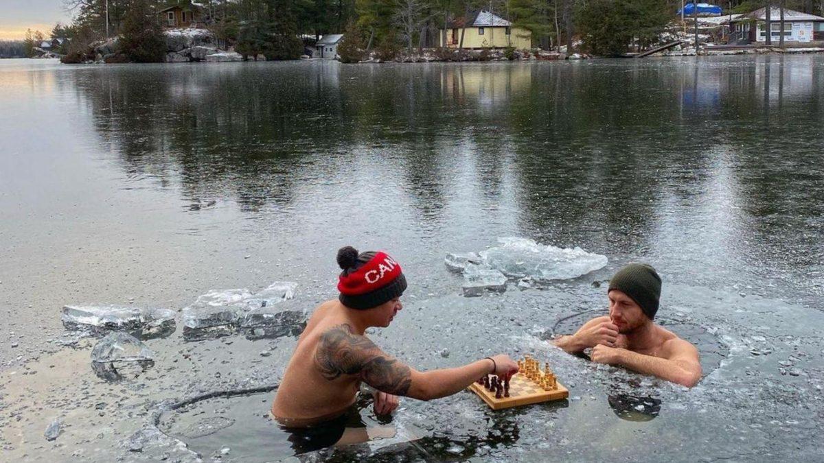 Dos hombres juegan una partida de ajedrez sin camisa y dentro de un lago helado